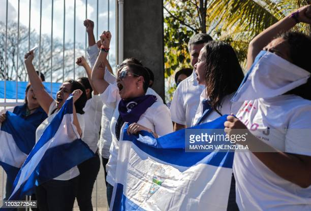Opposition demonstrators shout slogans asn they wave Nicaraguan flags during a protest outside the Divina Misericordia church in Managua on February...