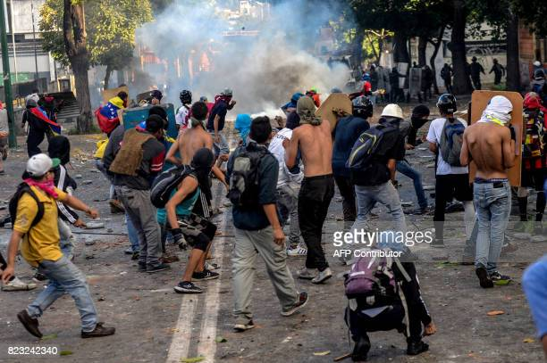 Opposition demonstrators skirmish with riot police ensuing an antigovernment protest in Caracas on July 26 2017 Venezuelans blocked off deserted...