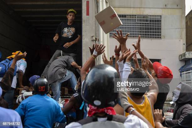 Opposition demonstrators steal bottles of liquid soap from a lorry during protest in Caracas on May 24 2017 Venezuela's President Nicolas Maduro...