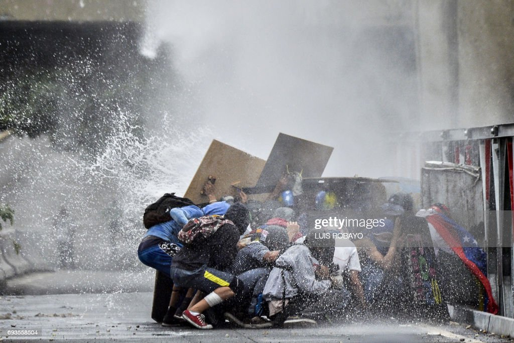 Opposition demonstrators taking cover behind their shields are hit by the jet from a riot police water cannon during a protest against the government of President Nicolas Maduro in Caracas on June 7, 2017. The head of the Venezuelan military, General Vladimir Padrino Lopez, who is also President Nicolas Maduro's defence minister, is warning his troops not to commit 'atrocities' against protesters demonstrating in the country's deadly political crisis. Tuesday's warning came after more than two months of violent clashes between protesters and security forces. /