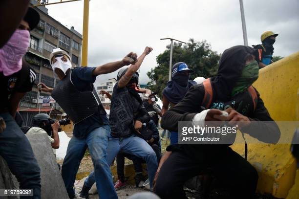 TOPSHOT Opposition demonstrators throw stones during an antigovernment protest in Caracas on July 20 2017 A 24hour nationwide strike got underway in...