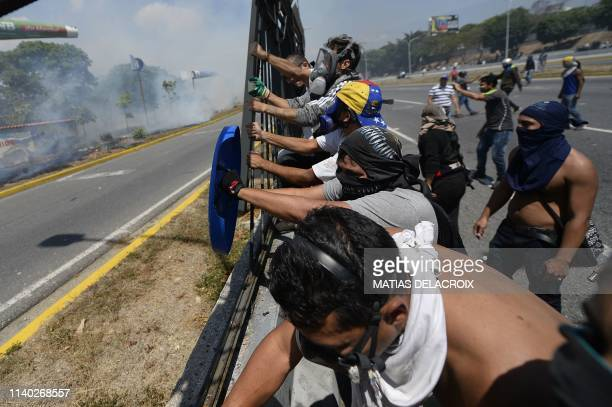 Opposition demonstrators try to bring down the fence around the La Carlota military base in Caracas during clashes with soldiers loyal to Venezuelan...