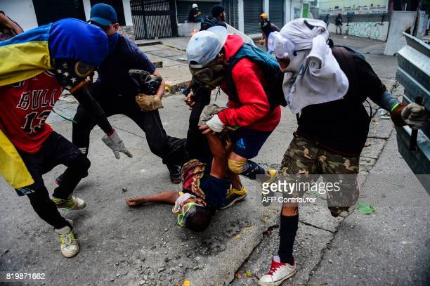 Opposition demonstrators try to help an injured mate during clashes with riot police within an antigovernment protest in Caracas on July 20 2017 A...