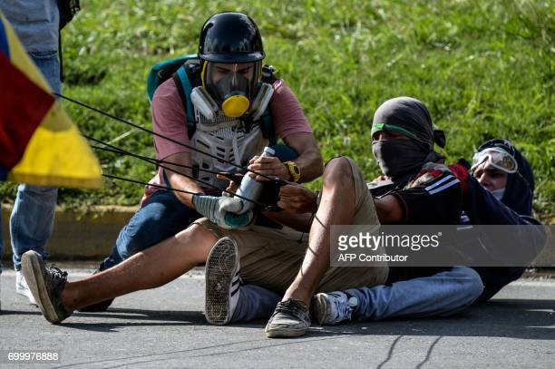 TOPSHOT Opposition demonstrators use a giant slingshot in clashes with the riot police during a protest against Venezuelan President Nicolas Maduro...
