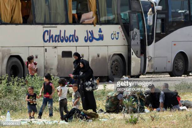 TOPSHOT Opposition fighters and their family members evacuated from the towns of Yalda Babila and Beit Saham south of Syria's capital under a...