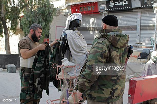 Opposition fighters dress up a dummy to fool sniper fire from regime forces during clashes in the northern Syrian city fo Aleppo on November 19 2013...