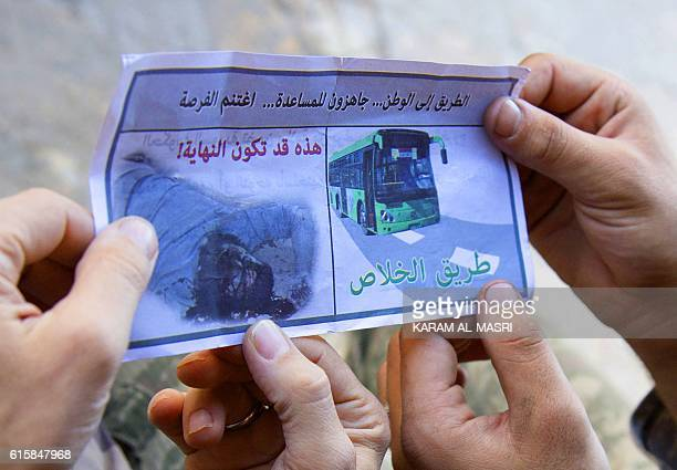 Opposition fighters from the Sham Legion look at a flyer reading in Arabic 'The road to the nationwe are ready to helpseize the opportunity The road...