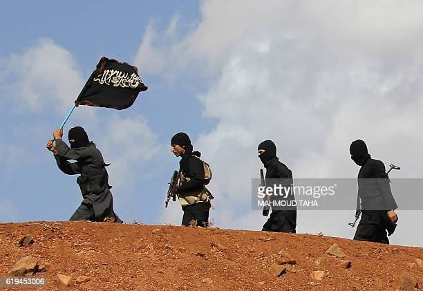 Opposition fighters from the Sham Legion walk flying an Islamist flag as they take part in training exercises for new recruits near Rastan on the...
