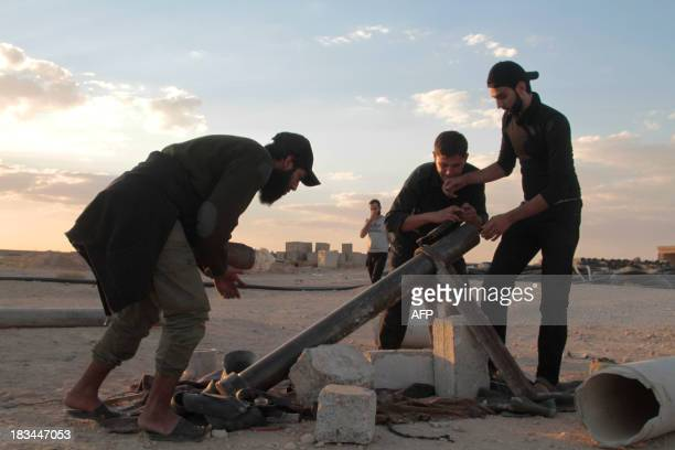 Opposition fighters prepare to fire a mortar shell during clashes with government forces in the northern rebelheld Syrian city of Raqqa on October 6...
