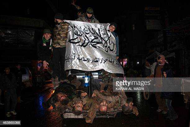 Opposition fighters wave the flag of Ahrar alSham brigade as they parade in the northern Syrian city of Aleppo on February 19 2015 the bodies of...