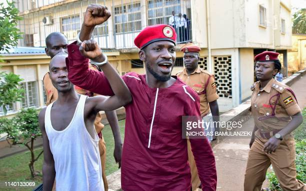 Opposition figurehead Hon Kagulanyi Robert aka Bobi Wine walks handcuffed together with another prisoner before boarding the prison bus leading him...