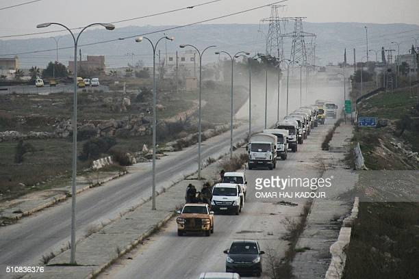 Opposition forces escort a convoy of aid vehicles heading to the governmentheld Shiite towns of Fuaa and Kafraya in Syria's northwestern Idlib...