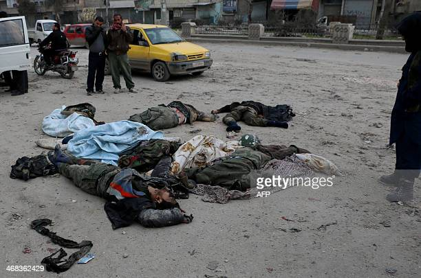 Opposition forces look at the bodies of members of the government forces lying on the ground in the village of Aziza on the southwestern outskirts of...