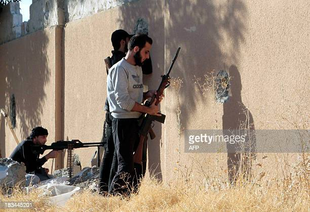 Opposition forces lookout through holes in a wall as they hold a position during clashes with government forces in the northern rebelheld Syrian city...