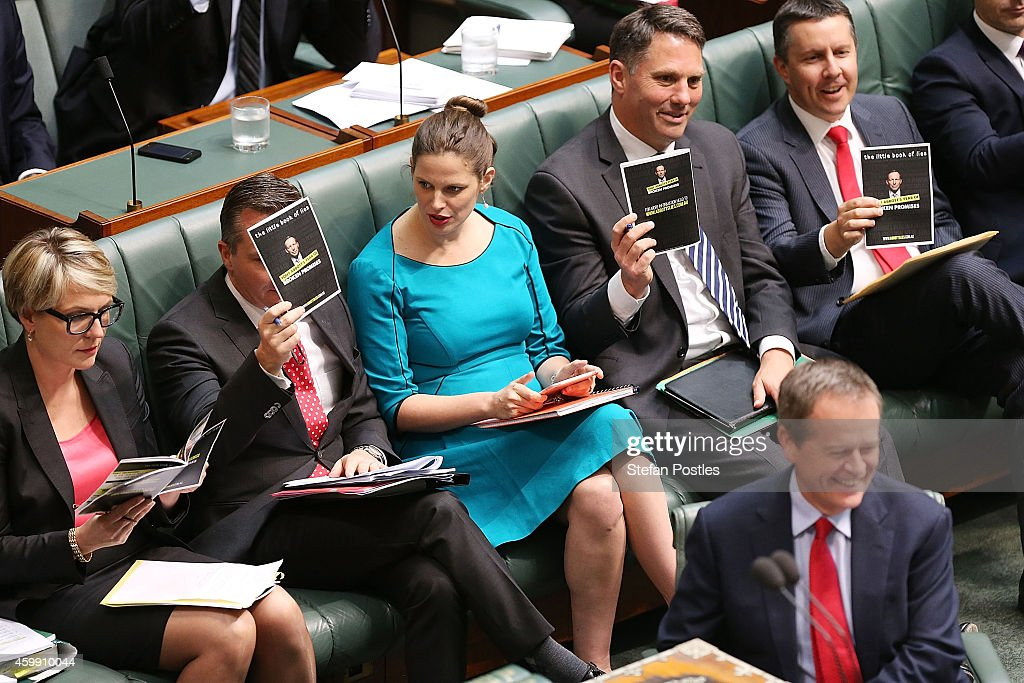 Opposition front bench hold up a prop book during House of Representatives question time at Parliament House on December 4, 2014 in Canberra, Australia. Today is the official last day of sitting at Parliament for 2014. Parliament will return on February 9, 2015.
