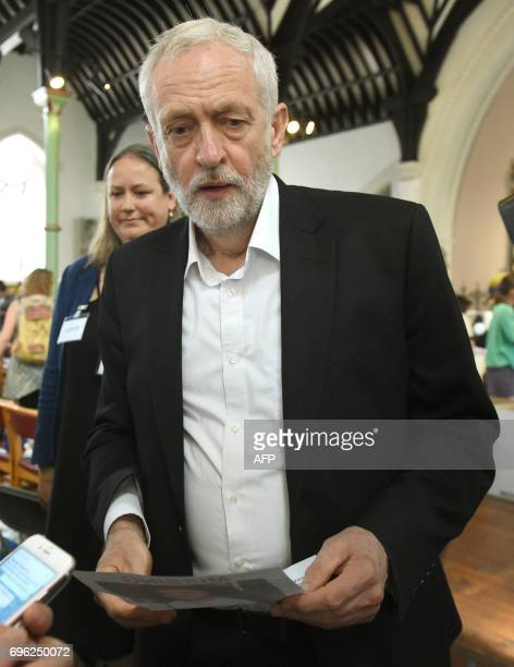 Opposition Labour leader Jeremy Corbyn meets staff and volunteers at St Clement's Church in west London on June 15 who have provided shelter and...