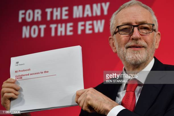 Opposition Labour party leader Jeremy Corbyn holds up a document during a press conference in London on December 6 2019