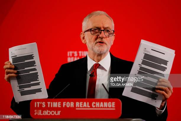Opposition Labour party leader Jeremy Corbyn holds up redacted documents from the government's UKUS trade talks during a press conference in London...
