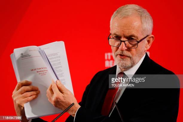 Opposition Labour party leader Jeremy Corbyn holds up unredacted documents from the government's UKUS trade talks during a press conference in London...