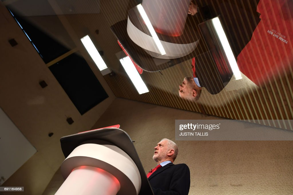 Opposition Labour Party leader Jeremy Corbyn is reflected in an autocue screen as he speaks during an election campaign event in Basildon, east of London on June 1, 2017. / AFP PHOTO / Justin TALLIS