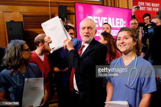 Opposition Labour party leader Jeremy Corbyn poses with NHS workers holding documents regarding the Conservative government's UKUS trade talks in...