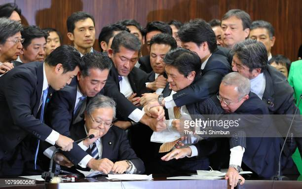 Opposition lawmakers gather at the Upper House Justice Committee chairman Shinichi Yokoyama as the Liberal Democratic Party and its junior coalition...