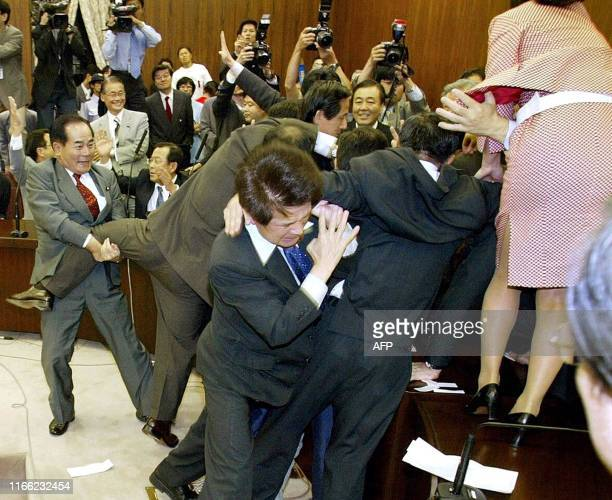 Opposition lawmakers rush to the chairman to stop the passage of the bill allowing Japanese Self Defense Forces to be sent to Iraq at the Upper...