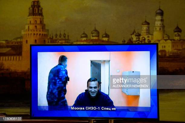 Opposition leader Alexei Navalny appears on a screen set up at a hall of the Moscow Regional Court via a video link from Moscow's penal detention...