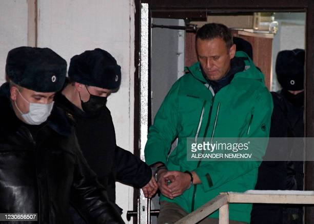 Opposition leader Alexei Navalny is escorted out of a police station on January 18 in Khimki, outside Moscow, following the court ruling that ordered...