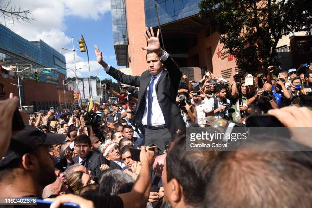 Opposition leader and reelected president of the National Assembly Juan Guaido speaks to the crowd as he attempts to enter the National Assembly...