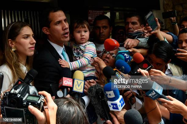 Opposition leader and selfproclaimed acting president Juan Guaido talks to the press as he holds his daughter Miranda next to his wife Fabiana...