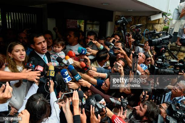 TOPSHOT Opposition leader and selfproclaimed acting president Juan Guaido talks to the press as he holds his daughter Miranda next to his wife...