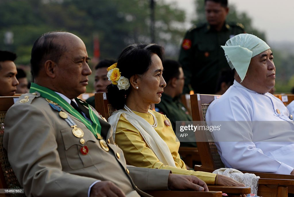 Opposition leader Aung San Suu Kyi (C), along with Major General Zaw Win (L), Deputy Minister for Border Affairs, attends a ceremony marking Myanmar's 68th Armed Forces Day at a parade ground in Naypyidaw on March 27, 2013. Suu Kyi attended Myanmar's Armed Forces Day for the first time.