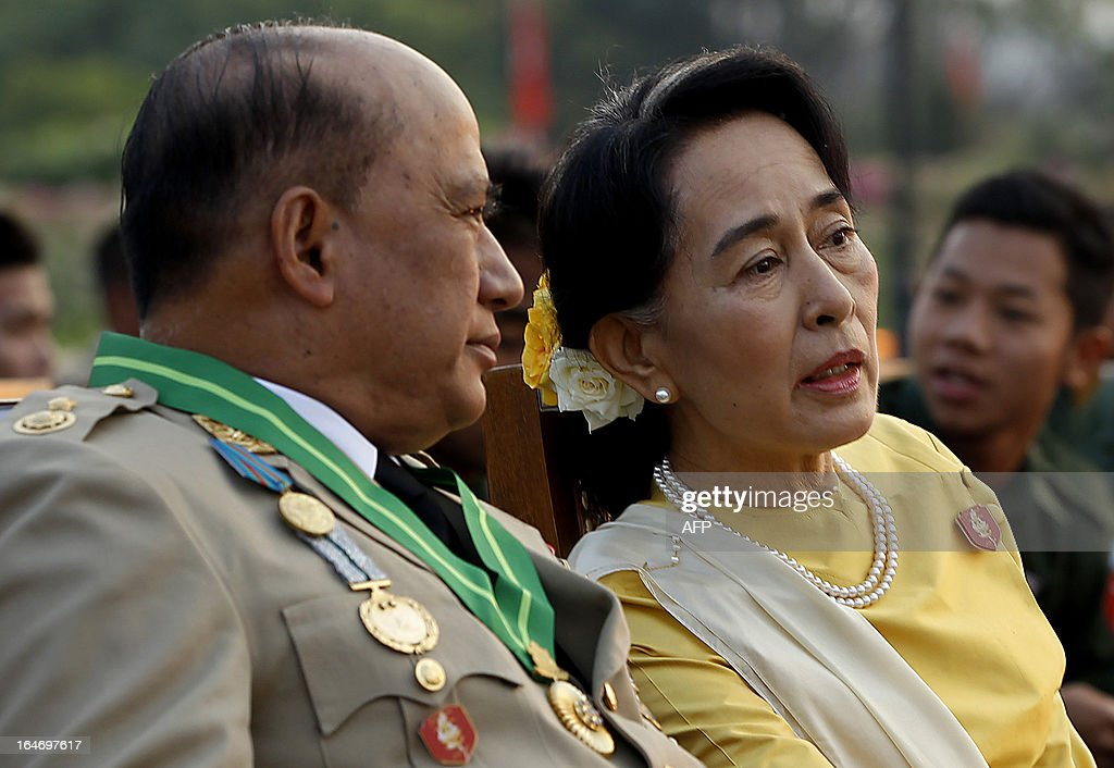 Opposition leader Aung San Suu Kyi (R) speaks with Major General Zaw Win (L), Deputy Minister for Border Affairs, during a ceremony marking Myanmar's 68th Armed Forces Day at a parade ground in Naypyidaw on March 27, 2013. Suu Kyi attended Myanmar's Armed Forces Day for the first time.