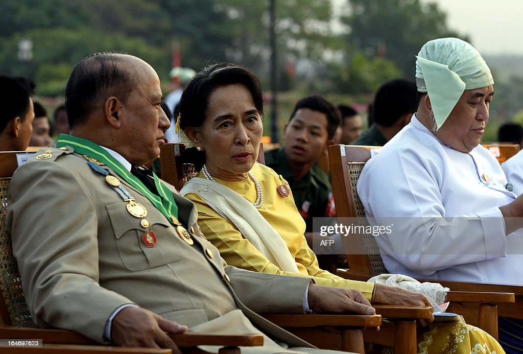 Opposition leader Aung San Suu Kyi (C) speaks with Major General Zaw Win (L), Deputy Minister for Border Affairs, during a ceremony marking Myanmar's 68th Armed Forces Day at a parade ground in Naypyidaw on March 27, 2013. Suu Kyi attended Myanmar's Armed Forces Day for the first time.
