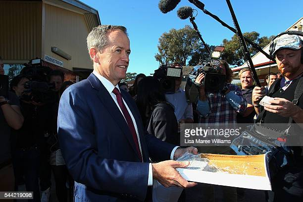 Opposition Leader Australian Labor Party Bill Shorten hands out lamingtons to the media during a visit to a polling booth at Colyton on July 2 2016...