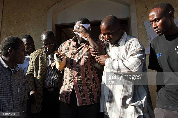 Opposition leader Kizza Besigye covers his eyes with a handkerchief as he is led by some of his followers following his fourth arrest this month in...