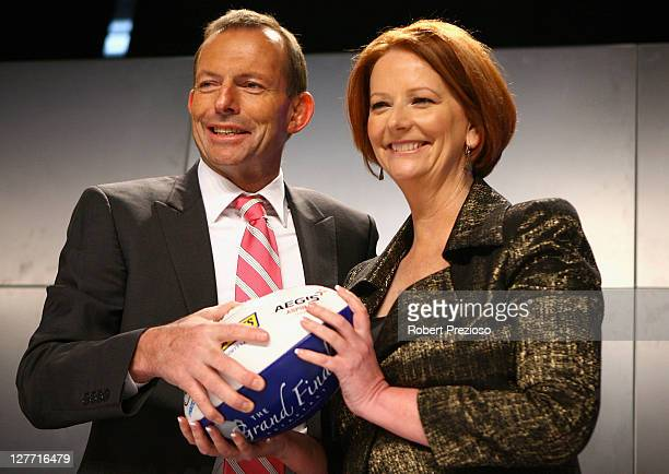 Opposition Leader Tony Abbott and Prime Minister Julia Gillard pose for photos during the North Melbourne AFL Grand Final Breakfast at Etihad Stadium...