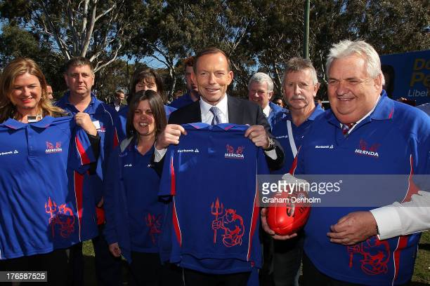 Opposition leader Tony Abbott poses with Liberal candidate for McEwen Donna Petrovich and members of Mernda Football Club on August 16 2013 in...