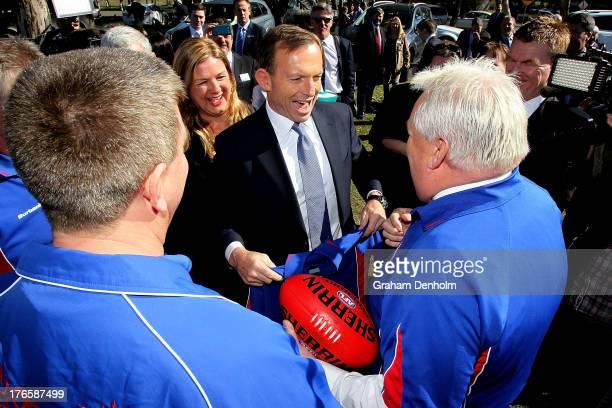 Opposition leader Tony Abbott shares a joke with members of Mernda Football Club on August 16 2013 in Melbourne Australia Abbott and Liberal...