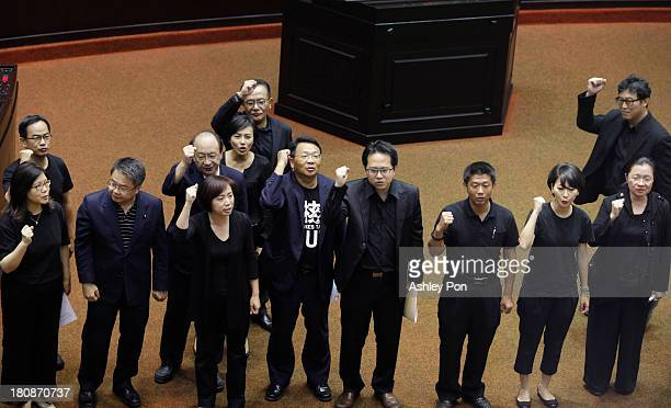 Opposition legislators dress in black shout slogan to demand Premier Jiang Yi-hua to step down during a protest at the Parliament on September 17,...