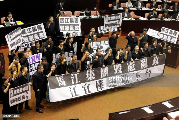 Opposition legislators hold placards and demand Premier Jiang Yi-hua to step down during a protest at the Parliament on September 17, 2013 in Taipei,...