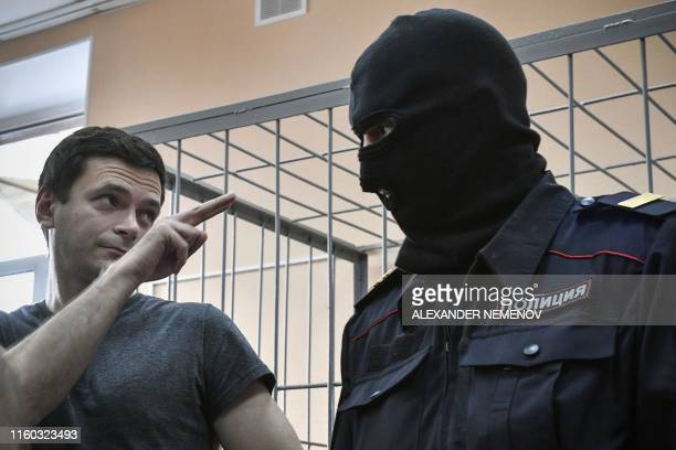 TOPSHOT Opposition member Ilya Yashin gestures towards a guard as he attends court hearings in Moscow on August 8 2019 Yashin was sentenced for...