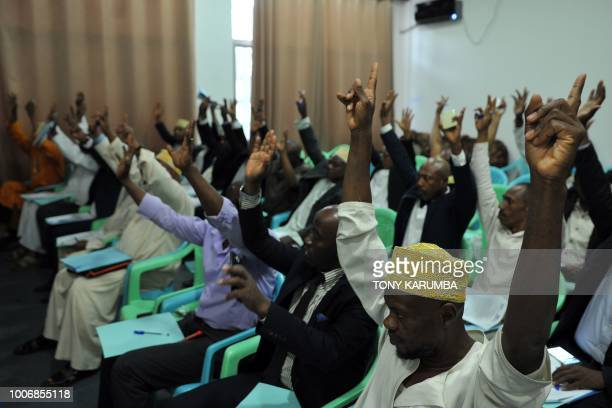 Opposition MP's raise their hands at a press conference to show their agreement with proposals to stop a referendum July 28 at parliament buildings...