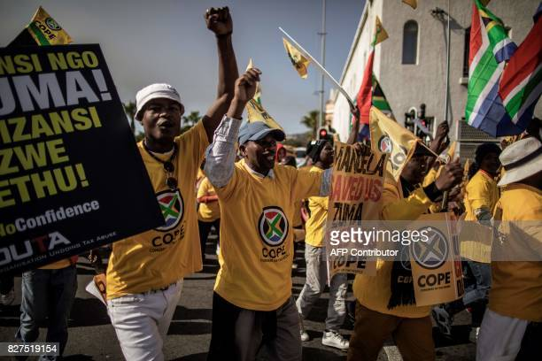 Opposition parties members hold signs and gesture as they march to support a Motion of no Confidence against South African president Jacob Zuma to be...