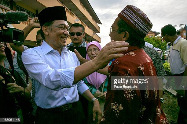 Opposition party leader Anwar Ibrahim greets a supporter after voting May 5 2013 in Penanti Malaysia Millions of Malaysians cast their vote on Sunday...