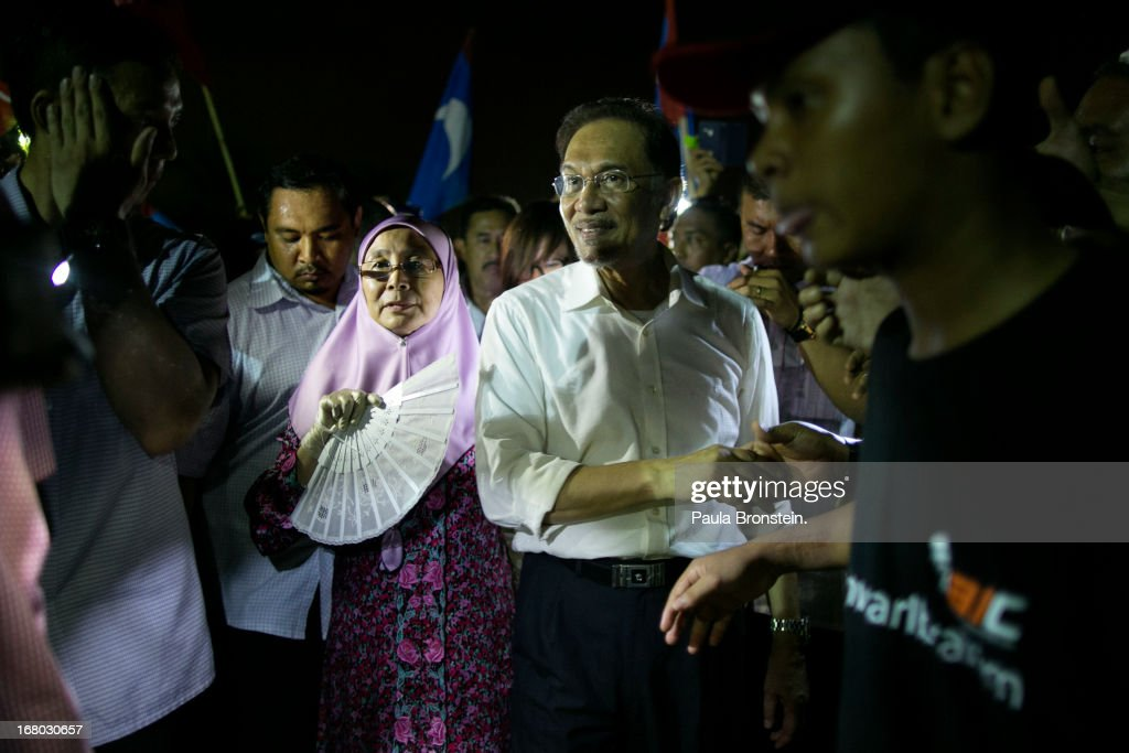 Opposition party leader Anwar Ibrahim shakes hands with his supporters with his wife during his last political rally before Malaysians vote tomorrow May 4, 2013 in Seberang Jaya, Malaysia. Millions of Malaysians will cast their vote tomorrow in one of the most tightly contested Malaysian election since independence in 1957. The opposition coalition, Pakatan Rakyat (People's Alliance), led by former deputy prime minister Anwar Ibrahim is seeking to gain power on a national level against the ruling party Barisan Nasional (National Front) coalition.