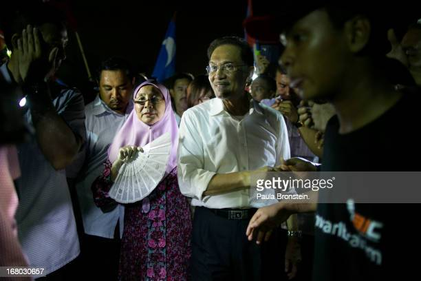 Opposition party leader Anwar Ibrahim shakes hands with his supporters with his wife during his last political rally before Malaysians vote tomorrow...