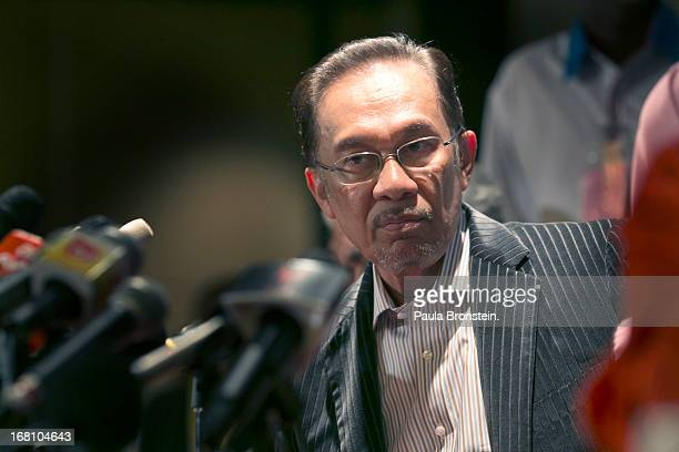 Opposition party leader Anwar Ibrahim waves after speaking to the media during a late evening press conference to discuss the results of the general...