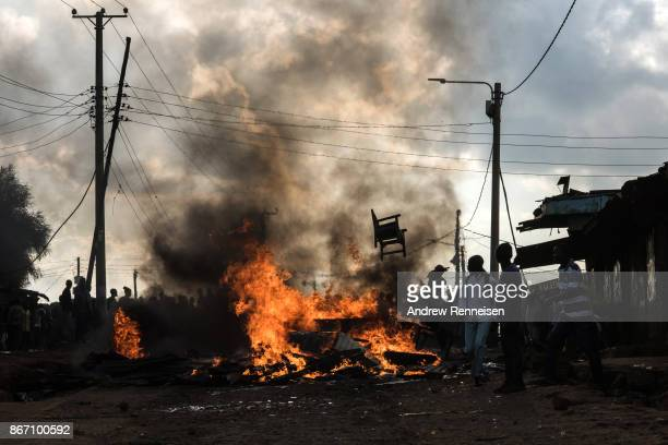 Opposition protestors stand in front of a flaming roadblock in the Kawangware slum on October 27 2017 in Nairobi Kenya Protests continued in...
